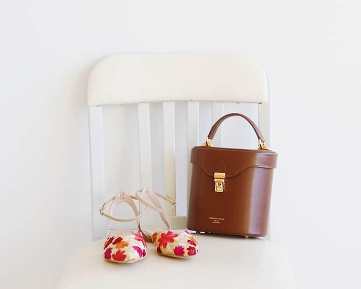 白い椅子の上に 茶色バッグ 花柄シューズ
