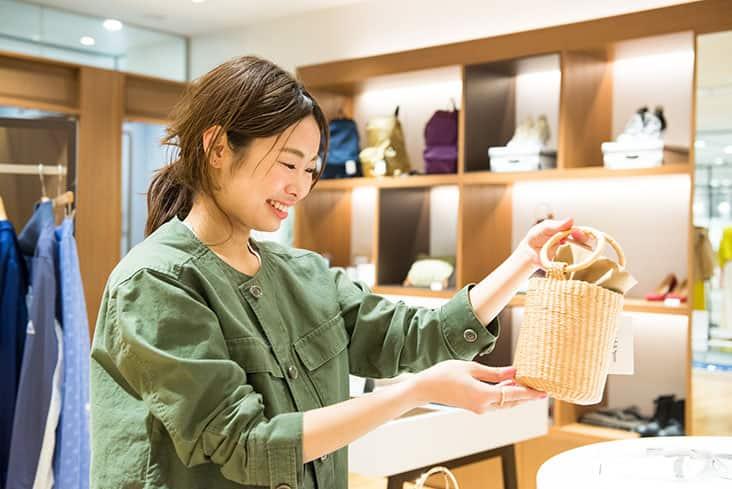 Spick滝沢さん 店内 かごバッグ選んでいるところ カーキジャケット着用